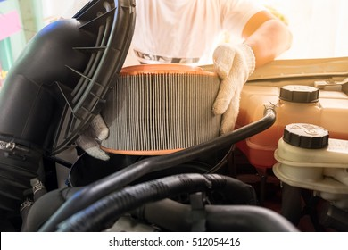auto mechanic wearing protective work gloves holding a dirty, air filter over a car engine for cleaning