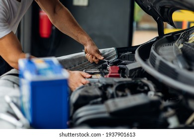 Auto mechanic worker checking and changing car battery. Car maintenance and auto service garage concept.