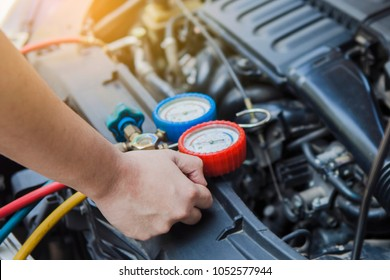 Auto mechanic Worker hands holding monitor to check and fixed car air conditioner system in car garage
