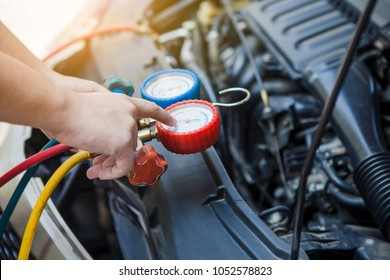Auto mechanic Worker hands holding and point to monitor to check and fixed car air conditioner system in car garage