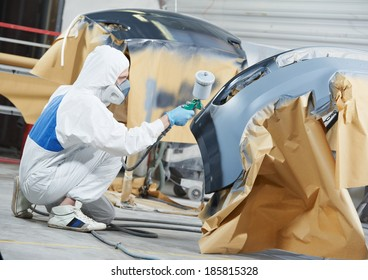 auto mechanic worker painting car bumper at automobile repair and renew service station shop by spraing black color paint