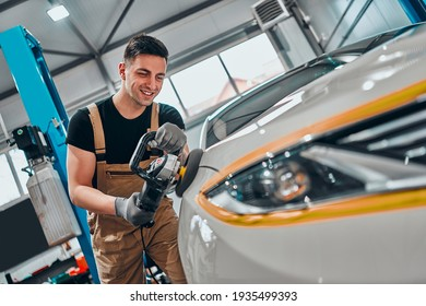 Auto mechanic worker polishing car at automobile repair and renew service station shop by power buffer machine. Selective focus. Close up view.