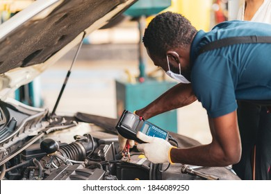 Auto mechanic working in garage, checking the battery ,car repair services concept