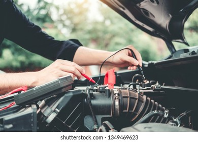 Auto mechanic working in garage Technician Hands of car mechanic working in auto repair Service and Maintenance check car battery.