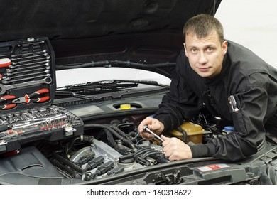 Auto mechanic working on a car engine repair