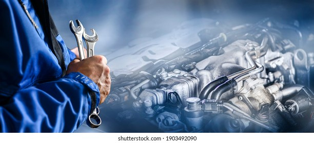 Auto mechanic working on car broken engine in mechanics service or garage. Transport maintenance wrench detial Wide banner or panorama photo.