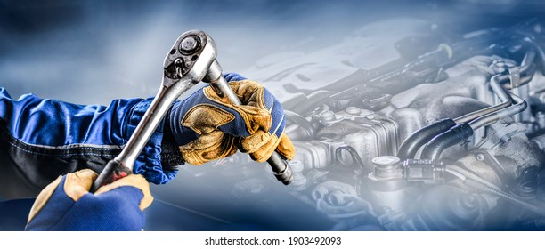 Auto mechanic working on car broken engine in mechanics service or garage. Transport maintenance wrench detial Wide banner or panorama photo. Copy space for text.