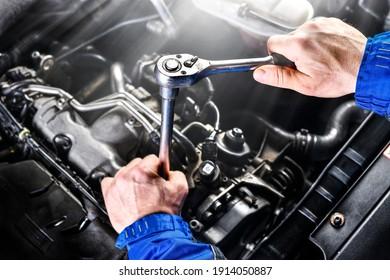 Auto mechanic working on car broken engine in mechanics service or garage. Transport maintenance wrench detial.