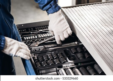 Auto mechanic with working tools For repair and diagnostics of cars in the garage Car