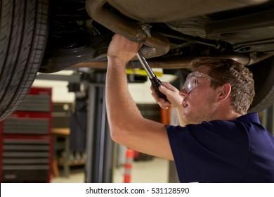 Auto Mechanic Working Underneath Car In Garage
