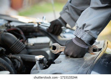 Auto mechanic with wrenches is standing near car open hood close up.