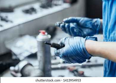 Auto mechanic's hands in protective gloves keeping spark plugs from car engine and searching for suitable washer,among other different details lying on working desk,to prevent from self-unscrewing