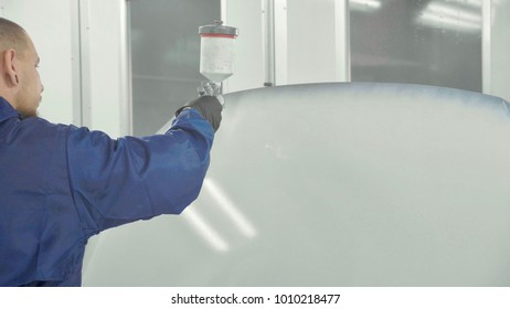 Auto painter spraying white paint on car spare bonnet in special booth. Painting vehicle parts at car service workshop