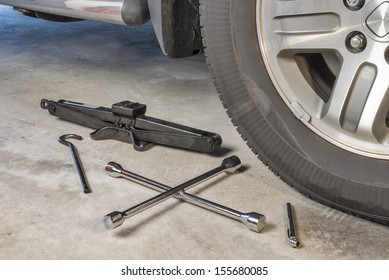 Auto parts that include a car jack, lug wrench and a tire pressure gauge on a garage floor.  Room for copy space.