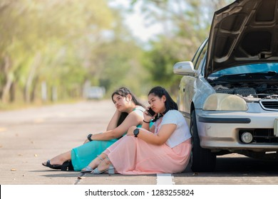Auto repair service, Insurance Concept - Teen driver using smartphone after car accident. Asian woman worry and stress a trouble with car engine crash overheat at the side of the road.