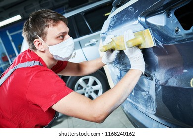 auto repairman grinding automobile body