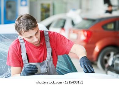 auto repairman plastering autobody bonnet