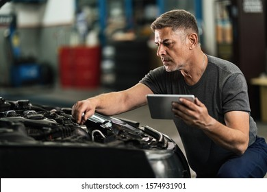 Auto repairman using touchpad while examining car engine in a workshop.