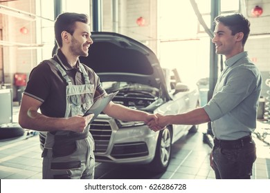 At the auto service. Handsome young auto mechanic in uniform and a client are shaking hands and smiling