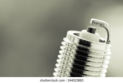 Auto service. New car spark plug as spare part of auto transportation on blurry gray background.