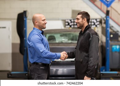 auto service, repair, deal and people concept - mechanic and customer or car owner shaking hands at workshop