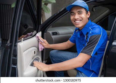 Auto service staff in blue uniform cleaning car with sponge and foam at car owner's home