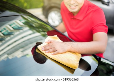 Auto service staff cleaning car rear windshield with microfiber cloth - car detailing and valeting concept