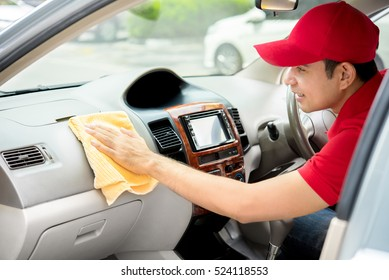 Auto service staff cleaning car interior - car detailing and valeting concept