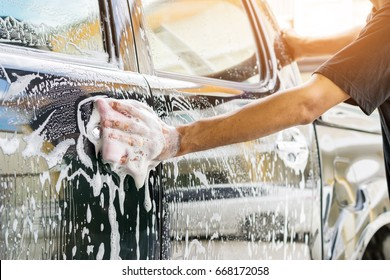 Auto service staff cleaning a car with sponge and car wash-car detailing and valet concepts.