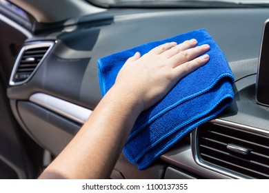 Auto service worker cleaning inside car with micro fiber cloth