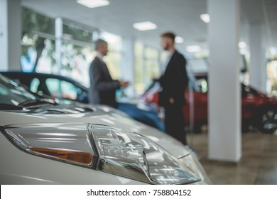 Auto showroom, dealer talking with buyer. Electro cars in moderm vehicle salon.