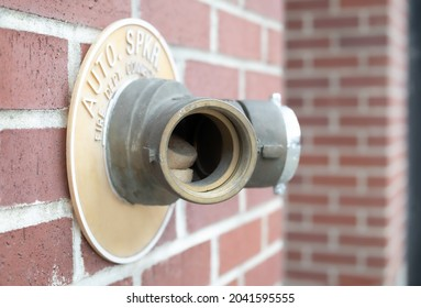 Auto sprinkler standpipe connector with missing cap and junk inside. Shows the importance of keeping the fire department connection covered. Outside of a building on brick wall. Selective focus.