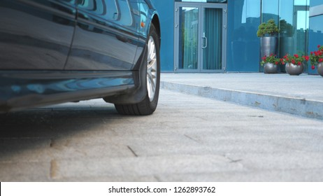 Auto stops near modern building. Businessman getting out of car and walking to office. Unrecognizable business man commuting to work. Confident guy in suit being on his way to job. Slow motion.