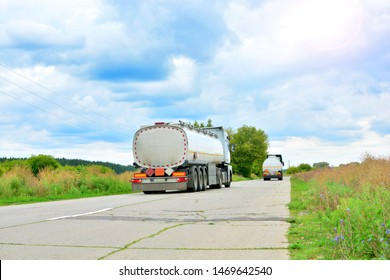 Auto tankers with big fuel tanks driving by the highway. Flammable cargo logistic.