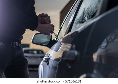 Ladrão de automóveis em balaclava preto tentando invadir carro com chave de fenda. Ladrão de carros, roubo de carro