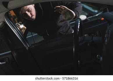 Auto thief looking to car interior. Car thief, car theft