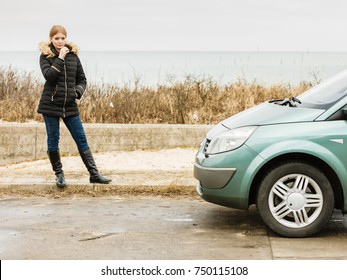 Auto traveling concept. Blonde driver woman in winter clothes standing next to her car.