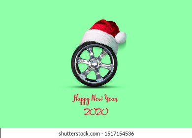 Auto wheel with a cap of Santa Claus. Green background. 2020 Happy New Year. Christmas background Greeting card for auto workshop. Auto mechanics.