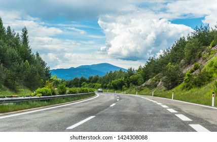 Autobahn or highway in the mountains with clear marking surrounded by vibrant green trees under blue sky. Stunning view and mountain in the background. The Alps, Austria