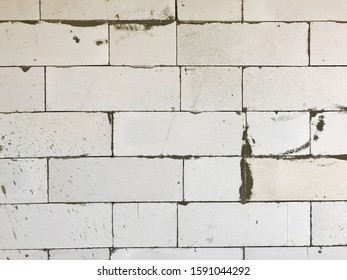 autoclaved aerated concrete (aac), lightweight concrete brick texture background during work in process of cement plastering at construction side, raw material for home building, house wall