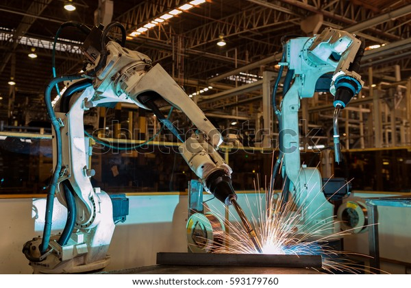 Automate industrial robots are welding automotive part in car factory