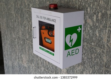 A automated external defibrillator AED inside a box attached to a tiled wall in a public place.
