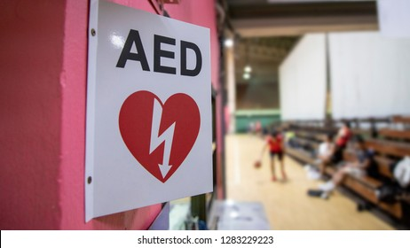 An automated external defibrillator symbol in front of the gymnasium. The AED using in emergency situation such as acute cardiac arrest. The basketball players was playing in blurred background.