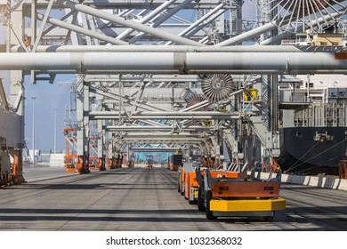 Automated Guided Vehicles moving shipping containers to and from gantry cranes in a port container terminal.