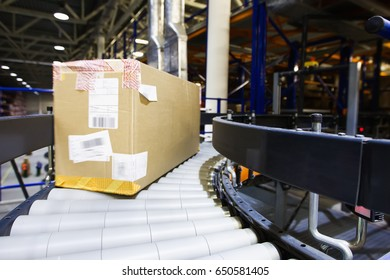 Automated modern warehouse. Boxes with spare parts moving on conveyor