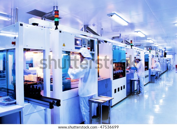 Automated production line in modern Solar silicon factory. Slow shutter speed with figures in motion.