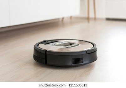 Automated vacuum cleaning robot powered by rechargeable battery in modern living room