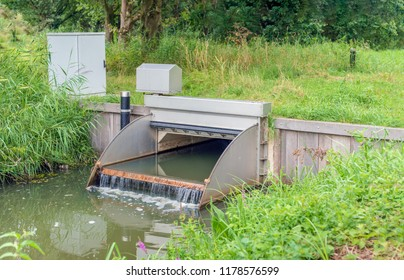 Automated working small weir in a stream manages the water level in a Dutch polder. The flowing water foams. The weir reflects in the mirror-smooth water surface of the ditch.
