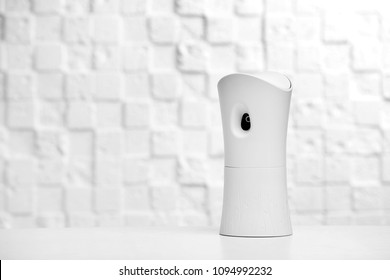 Automatic air freshener on table against light background