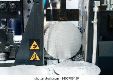 Automatic bandsaw sawing metal workpiece. From the cooling pipes supplied lubricity emulsion.